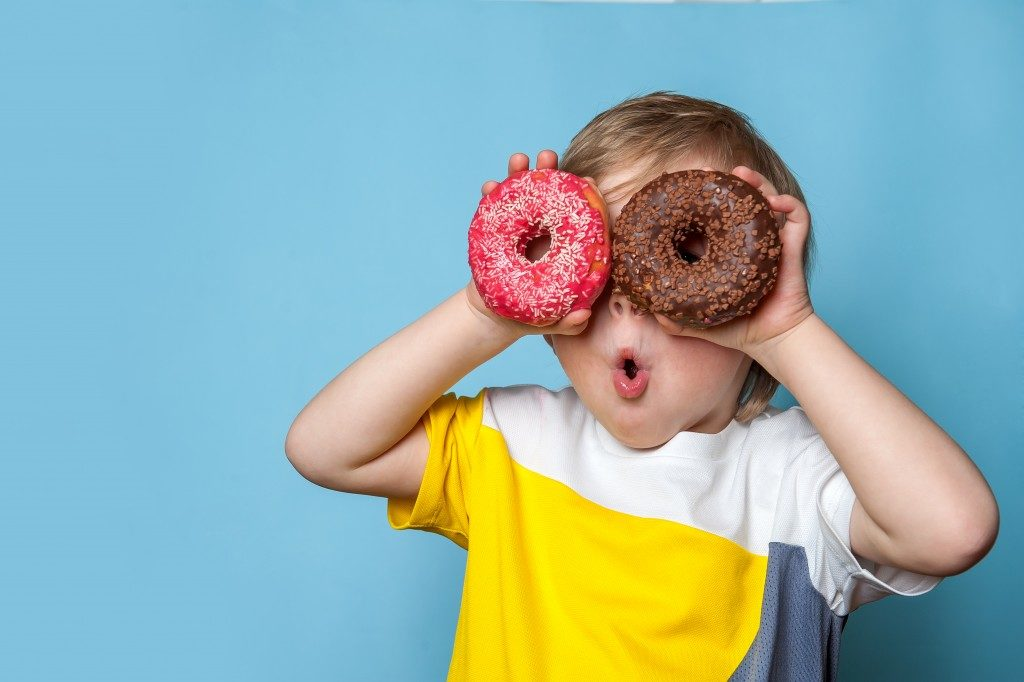 Kid holding two doughnuts