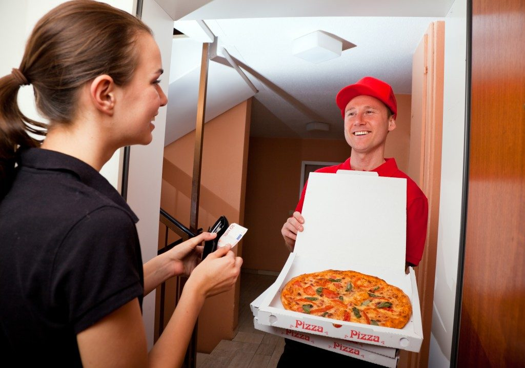 Woman paying the pizza delivery guy