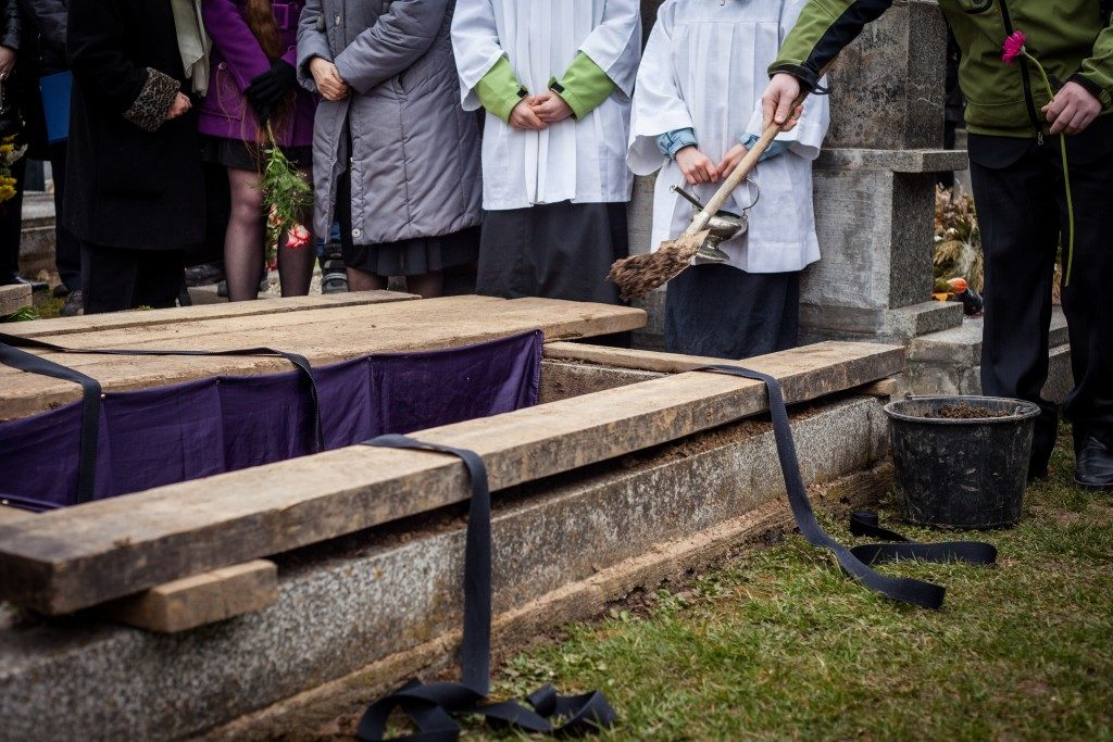 Mourners staying by the opened grave
