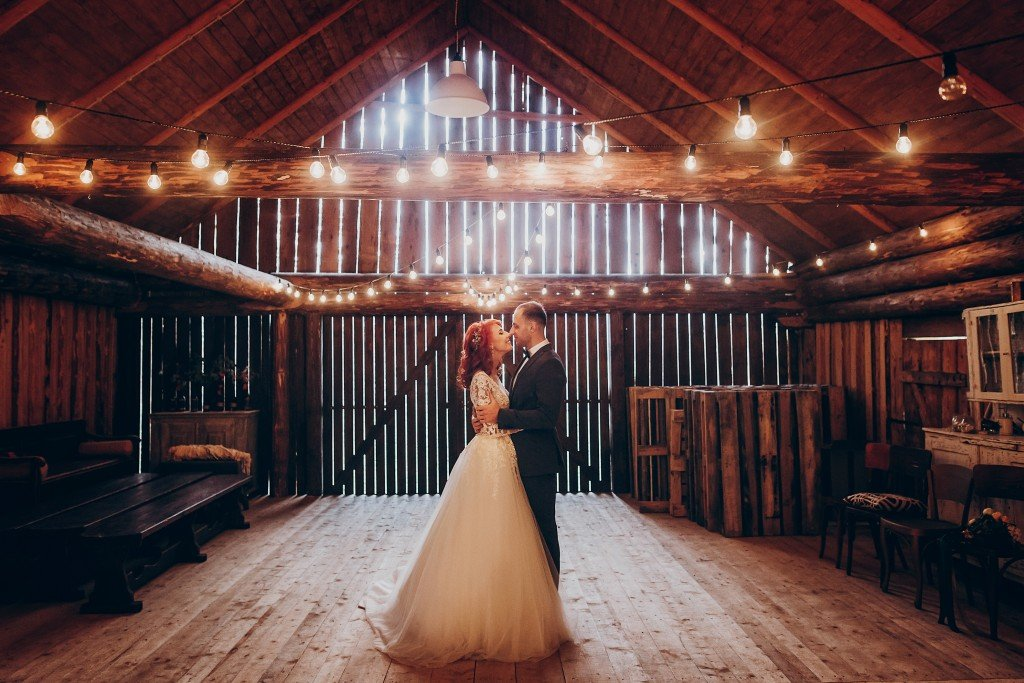 groom and wife dancing inside barnhouse