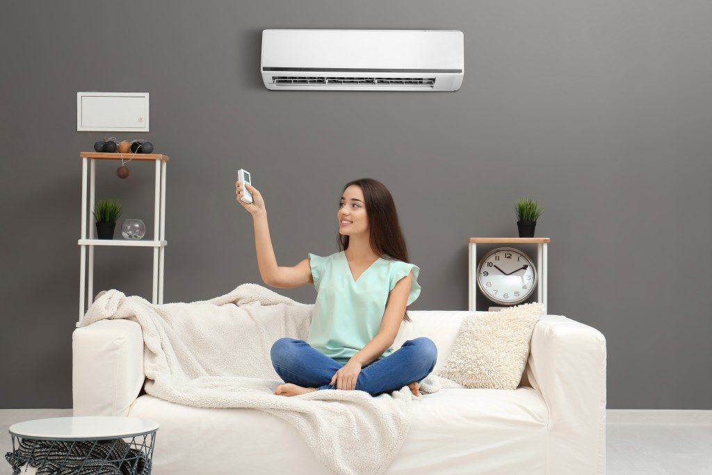 woman turning the airconditoner on in the living room