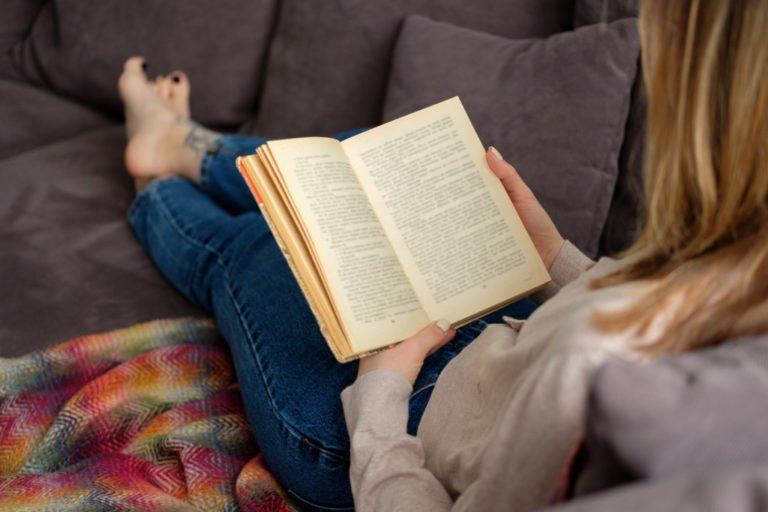 Female reading a book on the couch