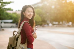 Asian female with backpack and notebooks