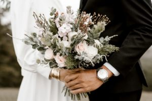 bride and groom standing while holding flowers